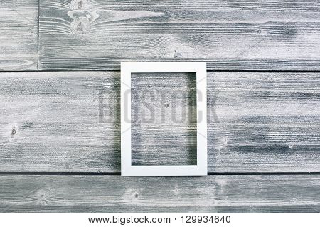 Empty see-through frame on antique wooden wall. Mock up