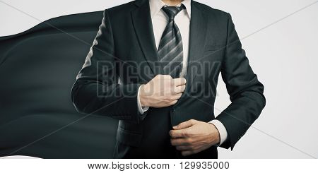 Businessman with black superhero cape on light background