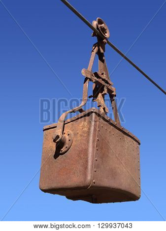 A Rusted mining bucket suspended on a cable.
