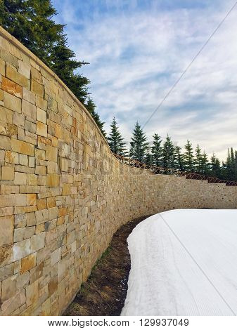 A curvy brick wall leading up to the resort.