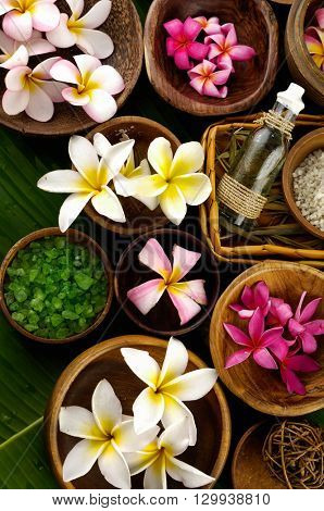 wooden bowl of color sea salt with ,candle ,massage oil and frangipani, on banana leaf