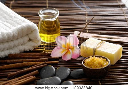 Zen rock and frangipani with towel,oil ,soap on bamboo mat