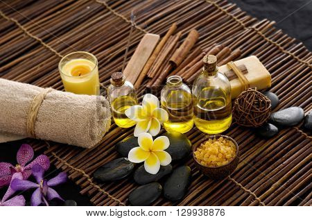 frangipani with stones ,candle, oil ,soap on mat background  frangipani with stones ,candle, oil ,soap on mat background