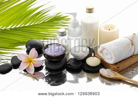 Spa still life with frangipani ,palm and black stone, candle,towel