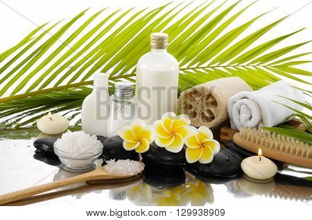 Spa still life with frangipani ,palm and black stone, candle,.towel,