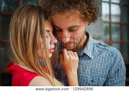 The curly-haired guy with the red-haired girl with freckles on the background of fabulous scenery of city and nature. Lovely couple of lovers on a walk in the city and nature. Tenderness emotion