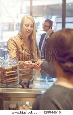 Young Blond Woman Making Payment At A Till