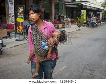Siem Reap, Cambodia - MAY 04, 2016: Unhappy homeless woman holding a baby