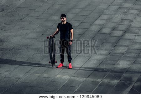 Stylish young hipster man standing with a longboard on a background of concrete tiles. Bearded man in bright sneakers, sunglasses and a stylish cap in the city urban landscape.