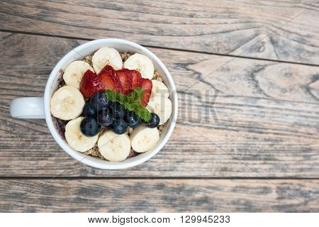 very delicious a small, round, black-purple drupe bowls with fresh strawberry, blueberry, banana and peppermint leaves in white cup on the wooden table. smoothie dessert is good for summer.