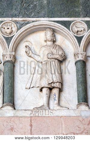 LUCCA, ITALY - JUNE 06, 2015: April, detail of the bas-relief representing the Labor of the months of the year, portal of the Cathedral of St Martin in Lucca, Italy, on June 06, 2015