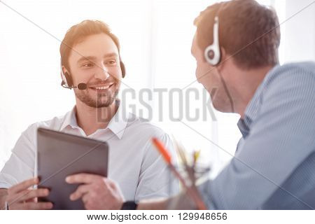 Like your job, Cheerful delighted smiling colleagues sitting at the table and talking with each other while working with headset with micro