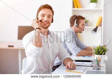 Diligent worker. Pleasant delighted handsome man using headset with micro and working in the call center while sitting at the table with his colleague