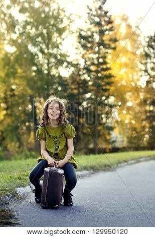 traveler girl with a suitcase outdoors