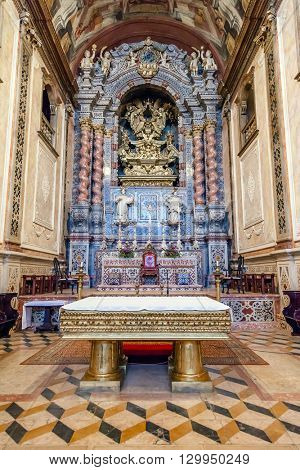 Santarem, Portugal. September 10, 2015: The baroque high altar in blue and gold colors inside the Santarem See Cathedral aka Nossa Senhora da Conceicao Church. 17th century Mannerist style.