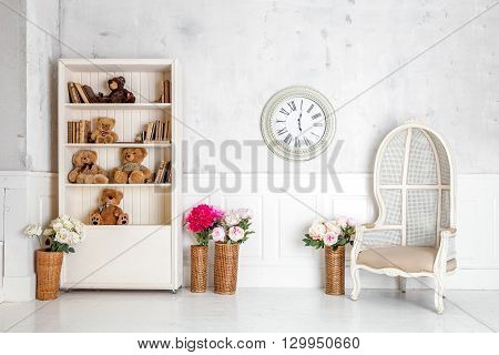 Modern light room interior with wardrobe, armchair and clocks on the wall