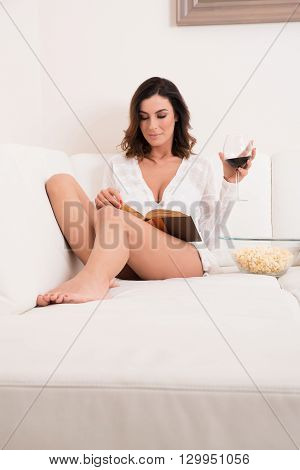 A beautiful young woman siting in underwear on a couch reading a book drinking wine and eating popcorn.