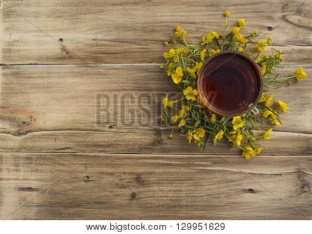 a Cup of tea and a wreath of buttercups