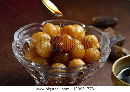 Sweet and natural date syrup is being poured on deep fried dumplings - Luqaimat. Arabic home made sweet delicacy.