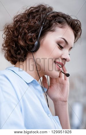 Involved in communication. Portrait of beautiful smiling cheerful woman using a headset with micro while working in the call center