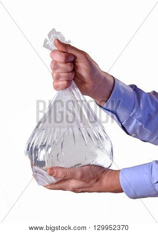 Hands holding transparent plastic water bag on white background.