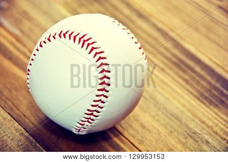 Baseball game. Baseball ball on wooden background. Vintage retro picture.