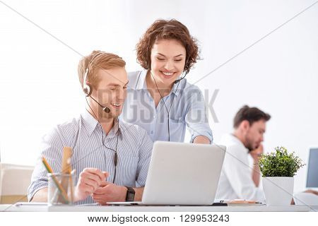 Work together. Cheerful delighted smiling colleagues working on the laptop and using headsets with micros while sitting in the office