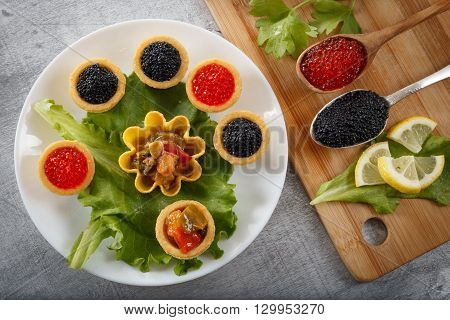 Tartlets filled with black caviar and cheese and dill salad on white plate and leaf against rustic wooden background with spoons full of caviar on bamboo cutting board horizontal top view