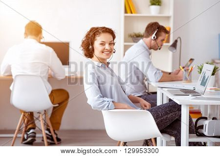 Like my work. Cheerful positive smiling woman sitting at the table  and using headset with micro while her colleagues sitting at the table in the background