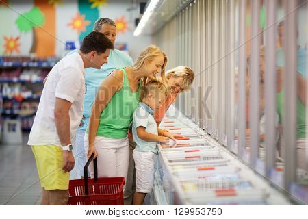 Young family shopping with the Grandparents in a supermarket standing with their young son at a food counter choosing produce