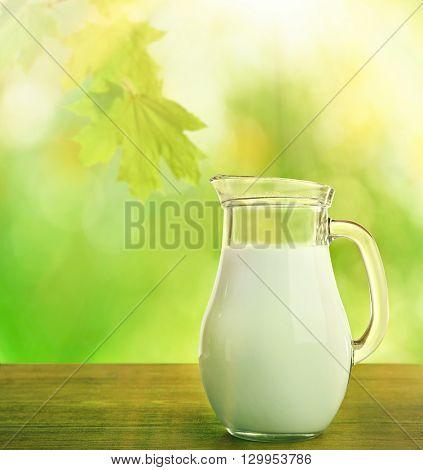 Fresh milk in jar on green nature background