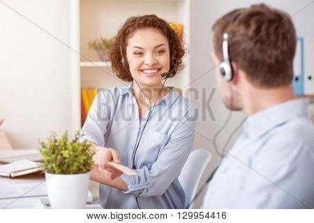 That is for you. Pleasant delighted smiling colleagues sitting at the table and using headsets with micros while expressing gladness.