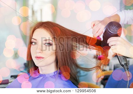 Young woman hairdresser do hairstyle girl in beauty salon, over blurred lights
