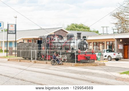 AVONTUUR SOUTH AFRICA - MARCH 5 2016: An unidentified person in a wheelchair in front of an historic narrow gauge Class NG15 steam engine used on the Apple Express on display in Avontuur