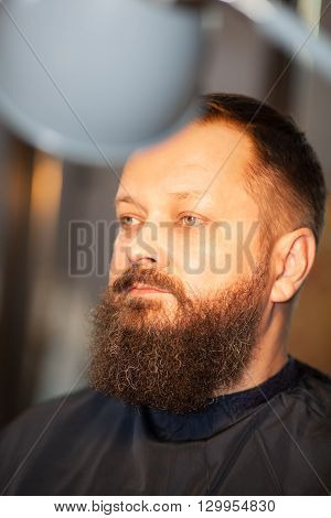 Attractive middle-aged bearded man in a barber shop having his beard, hair and mustache trimmed, closeup head shot