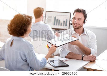 Take it. Pleasant delighted smiling colleagues sitting at the table and holding folder while using headsets with micros