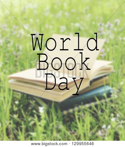 Stacked books in grass. World Book Day poster