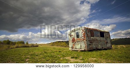 Old beaten up trailer in the middle of spring field and stormy clouds