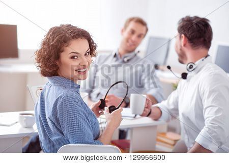 With positive attitude. Cheerful beautiful smiling woman holding headphones and sitting in the office while her colleague talking in the background