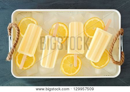 Homemade Lemon Yogurt Popsicles In A Rustic Ice Filled Tray With Fresh Fruit Slices