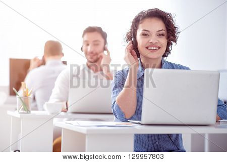 At you disposal.  Positive, smiling beautiful woman sitting at the table and using headset with micro while her colleagues working in the background