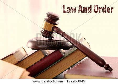 Gavel with pile of books on light blurred background. Law and order concept