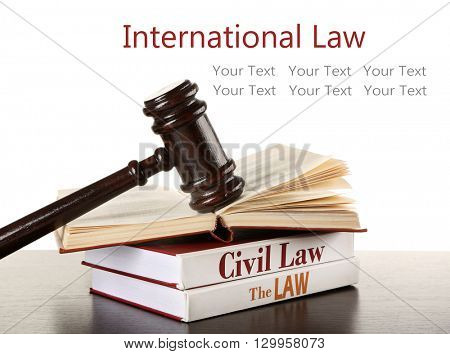 Gavel and books on wooden table on white background. International law concept