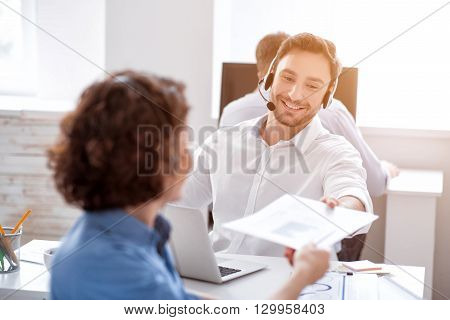 Cooperate with people. Pleasant delighted smiling colleagues sitting at the table and holding folder while using headsets with micro