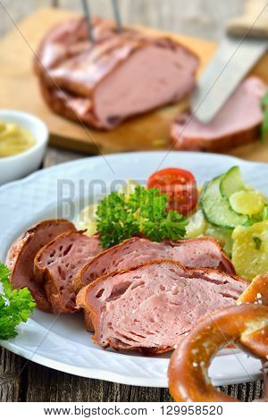 Portion of oven fresh Bavarian meat loaf with potato salad, a pretzel and mustard