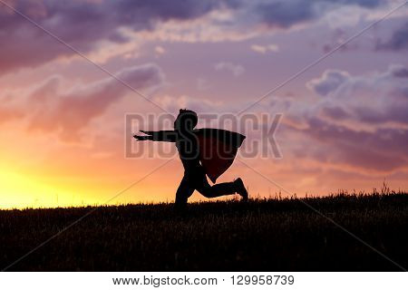 A young boy wearing a cape plays a super hero at sunset.