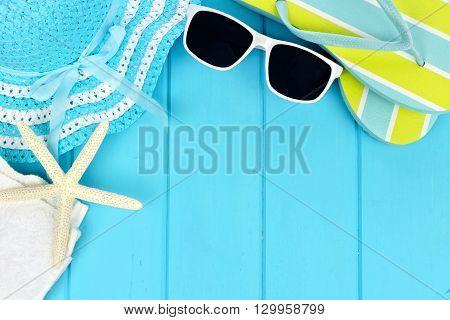 Summer corner border of beach items on blue wooden background