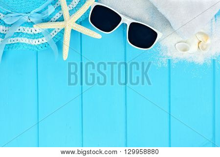 Summer top border of beach items and sea shells on blue wooden background