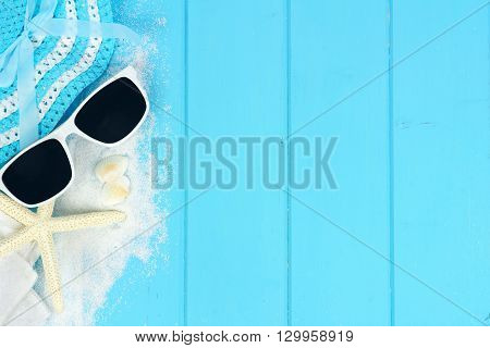 Summer side border of beach items and sea shells on blue wooden background