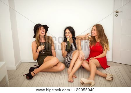 Three beautiful girls getting drunk at home.